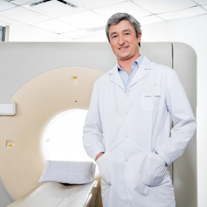 Portrait of mature male doctor standing by CT scan machine with hands in pockets