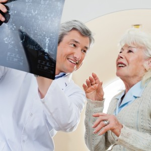 Happy mature male doctor with senior female patient looking at x-ray