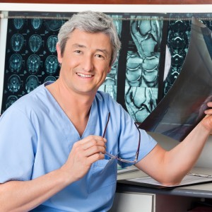 Portrait of mature male radiologist at desk smiling while holding x-ray