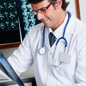 Mixed race male radiologist smiling while reviewing x-ray at clinic
