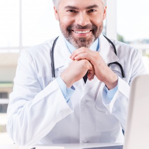 Always ready to help. Confident mature grey hair doctor leaning his face on hands and smiling while sitting at his working place