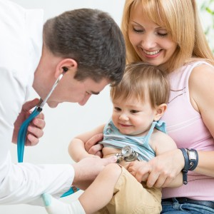 doctor examining kid patient with stethoscope