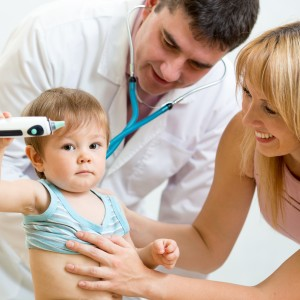 Pediatrician doctor examining kid boy. Mother holding baby.