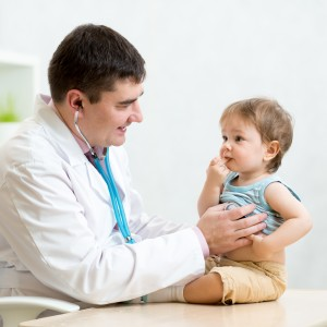 pediatrician examining heartbeat of baby boy with stethoscope