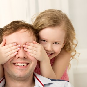 Father and daughter playing at home. Little girl closing dads eyes with hands and laughing. Family fun together