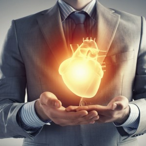 Close up of businessman holding digital glowing heart in palm