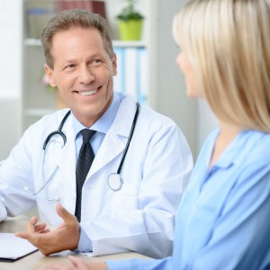 In a good mood. Pleasant overjoyed smiling professional doctor holding pen and sitting at the table while talking with his patient